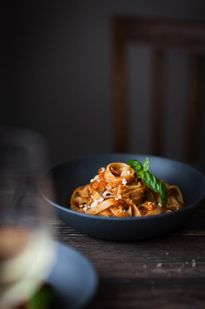 a head on image of a bowl of pasta on a wooden table.