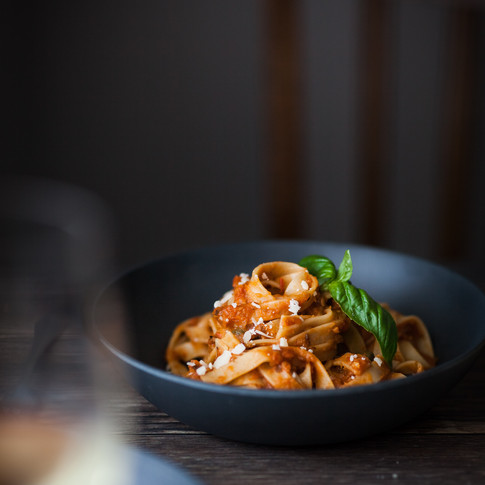 portrait of a plate of pasta in a blue bowl with a chair in the background.
