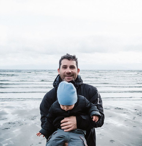 portrait of a man smiling in a black raincoat while holding his son at the beach.
