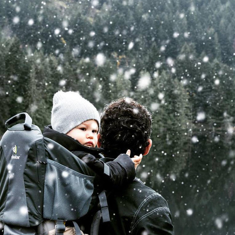 portrait of a baby in a hiking backpack on dads back during a snowfall.