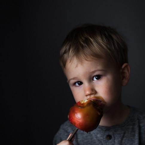 a portrait of a child eating a red candy apple against a black background.