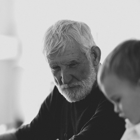 black and white portrait of an older man wearing a black shirt and a small child in the foreground.