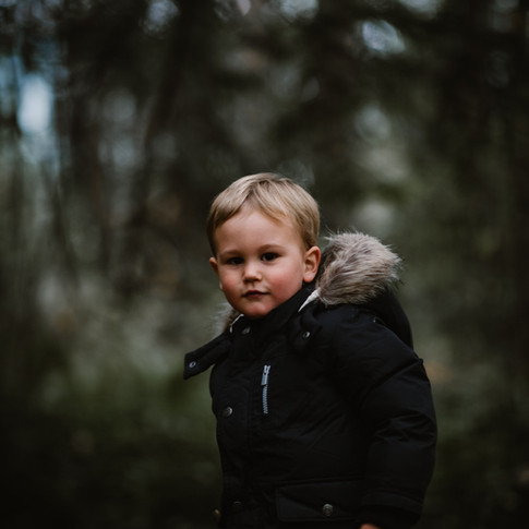 a portrait of a small child wearing a fur lined coat in the woods.