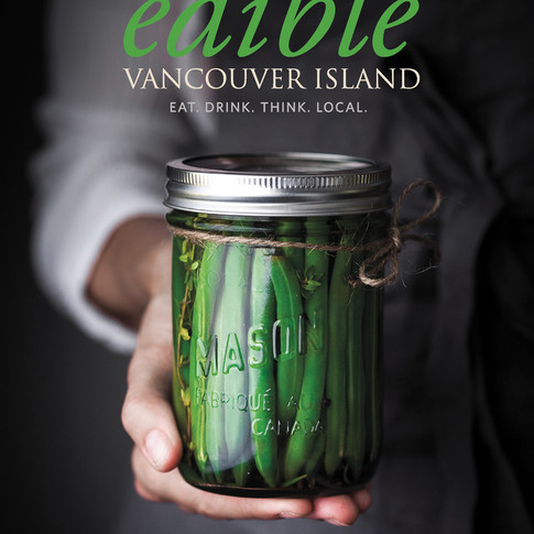 Edible Vancouver Island Magazine cover shot of a person holding a jar of pickled beans.
