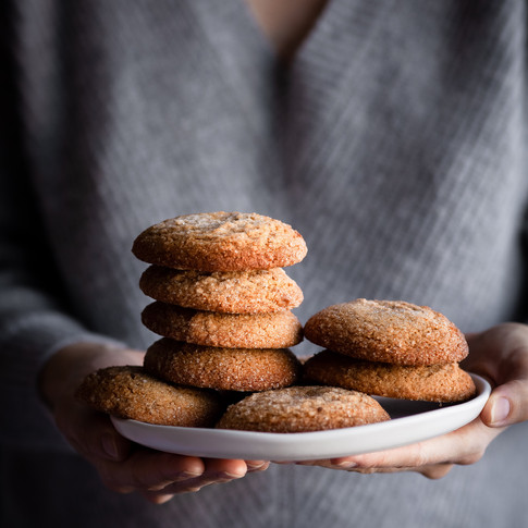 portrait of a stacks of cookies on a white plate beging held by a person wearing a grey sweater.