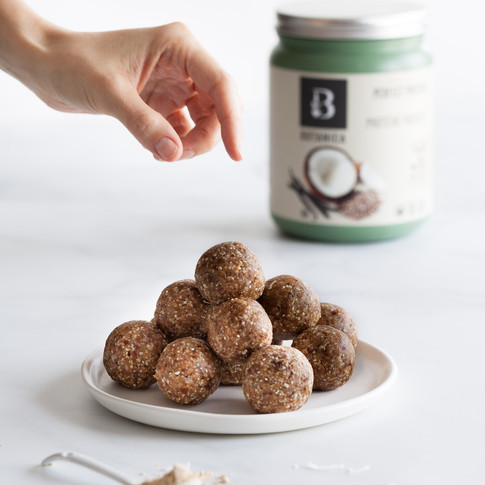 portrait of a energy balls against a white surface with a hand reaching for one and a bottle of protien powder in the background.