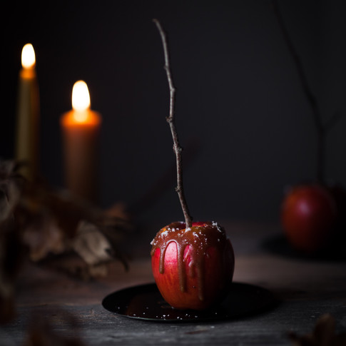portrait of a caramel apple with candles and dry leaves in the background.