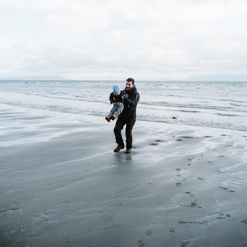 landscape image of a man holding his son at the beach at low tide.
