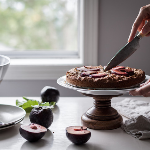 horizontal portrait of a person cutting into a cake on a cakestand with plums and plates in the foreground.