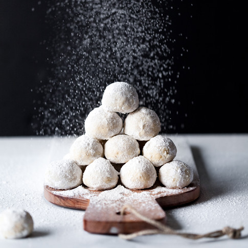 portrait of a stack of snowball cookies on a wood cutting board being dusted with icing sugar.