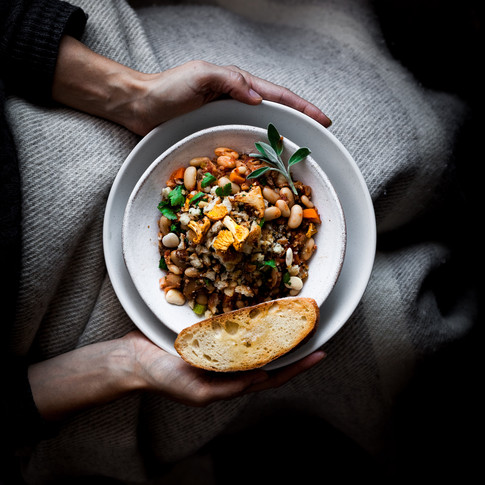 overhead image of person covered in a lap blanket holding a plate of stew.