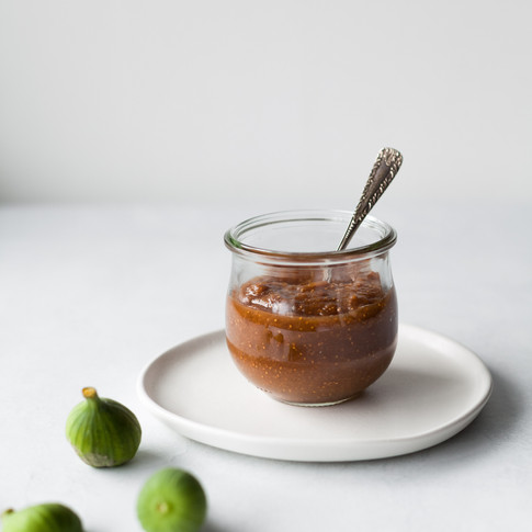 portrait of a jar of fig jam against a white surface with a spoon sticking out and two fresh figs on the left