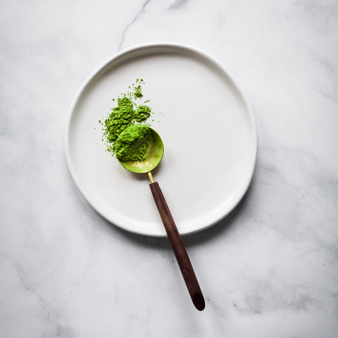 overhead portrait of a golden spoon filled with matcha powder on a white plate on a marble surface.