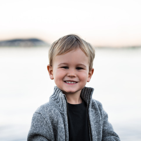portrait of a small child smiling with the ocean in the background.