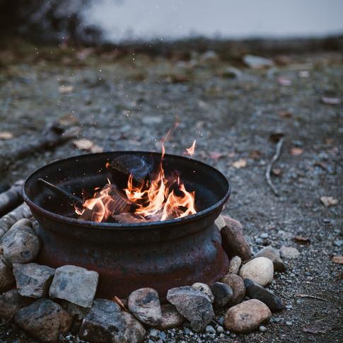 portrait of a campfire on a rocky beach.