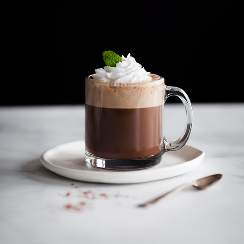 portrait of a mug of hot coco with whipped cream, mint leaves on a white plate with a spoon on the right.