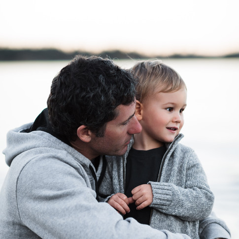 portrait of a dad and child against an ocean at sunset.