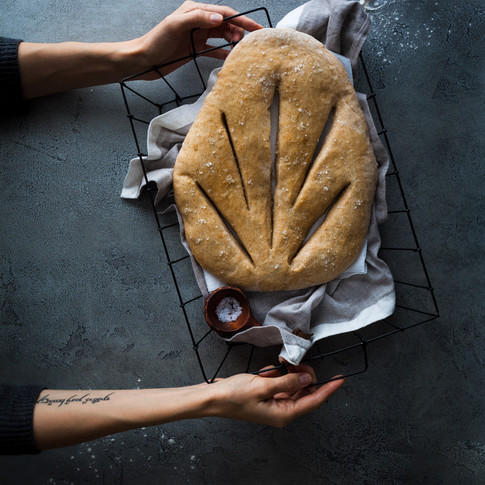 overhead portrait of fougasse bread in a basket held by two hands.