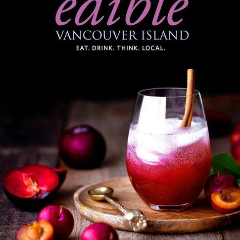 Edible Vancouver Island Magazine cover shot of a glass of plum shrub with plums and a golden spoon on the left.