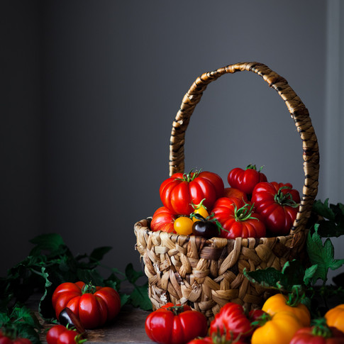 portait of a basket of heirloom tomatoes on a wooden surface.