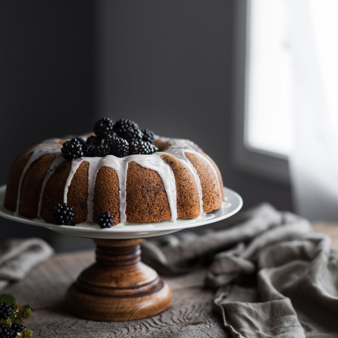 a portrait of a bundt cake on a stand sitting by a window.