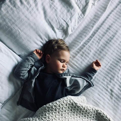 overhead portrait of a baby sleeping on a bed with a beige knit blanket.