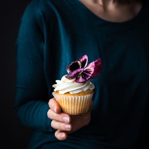 portrait of a person in a green shirt holding a vanilla cupcake with a purple flower ontop.