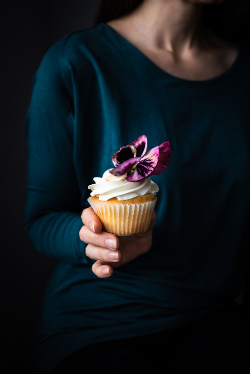 portrait of a person on a green short holding a vanilla cupcake with a purple flower on top.