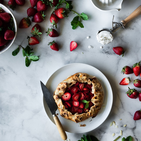 overhead image of a strawberry galette on a marble surface with a knife, lemon juicer, icecream scoop and fresh strawberries.