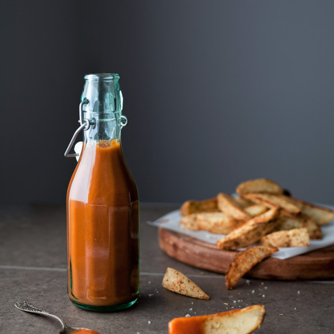 portrait of a glass bottle of ketchup on a grey surface with french fries in the background.