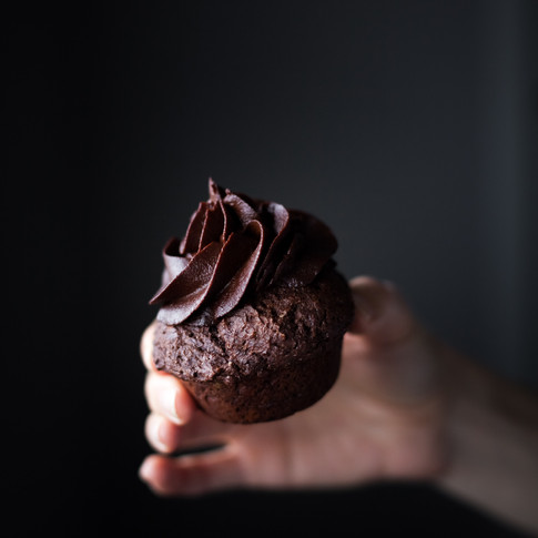 closeup portrait of a chocolate cupcake being held.