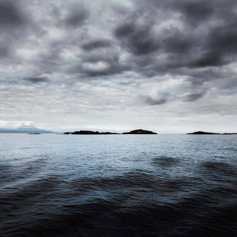 horizontal landscape image of dark stormy sea with a small island in the background.