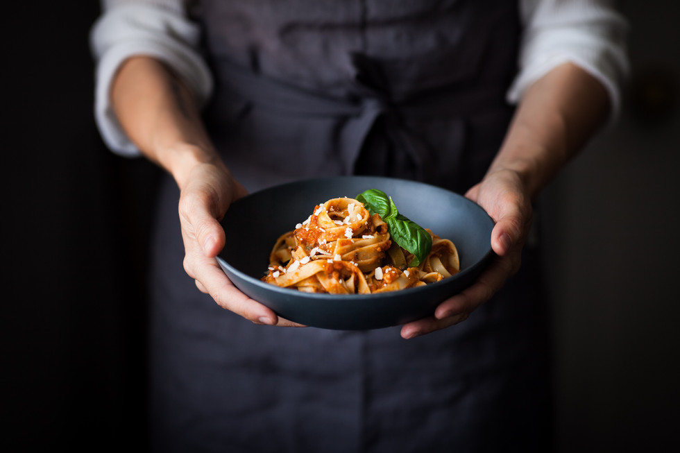 a close up image of a cook holding a bowl of pasta.