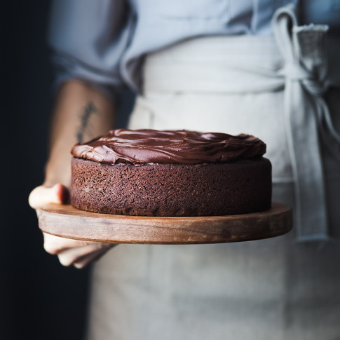 portrait of a person in a blue shirt with a beige apron holding a chocolate cake.
