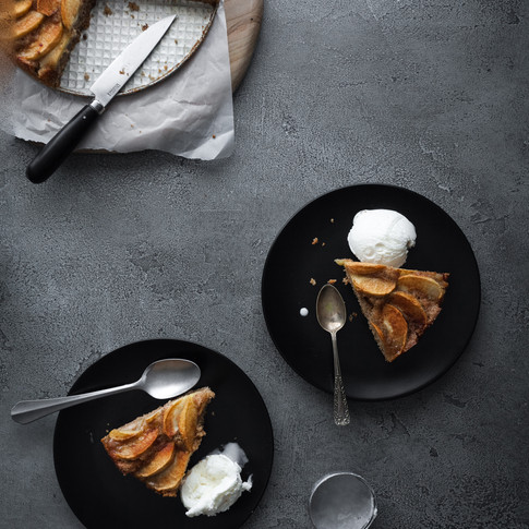 overhead portrait of an apple cake with two slices on black plates with ice cream.
