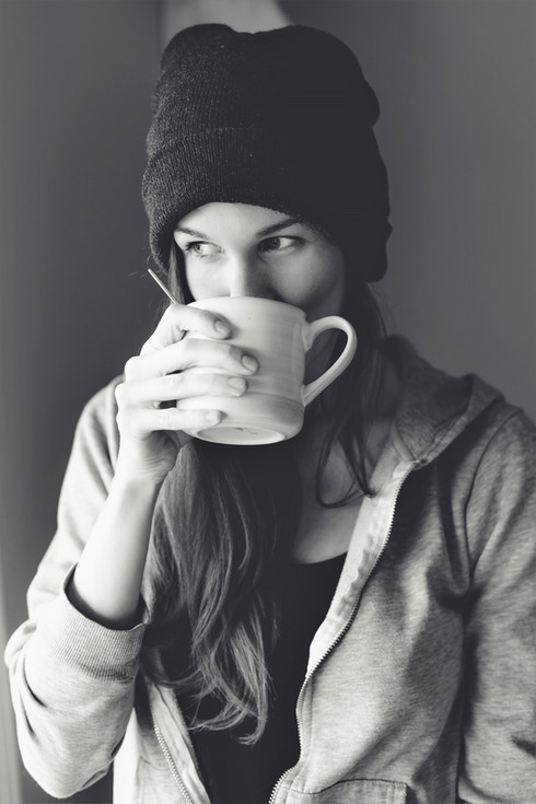 a black and white image of Heidi Richter drinking a cup of coffee.