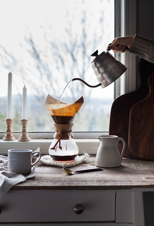 a head on image of  hot water being poured over coffee grounds sitting infront of a window.