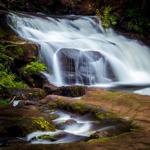 portrait of a rushing water fall running over a large rock in the woods.