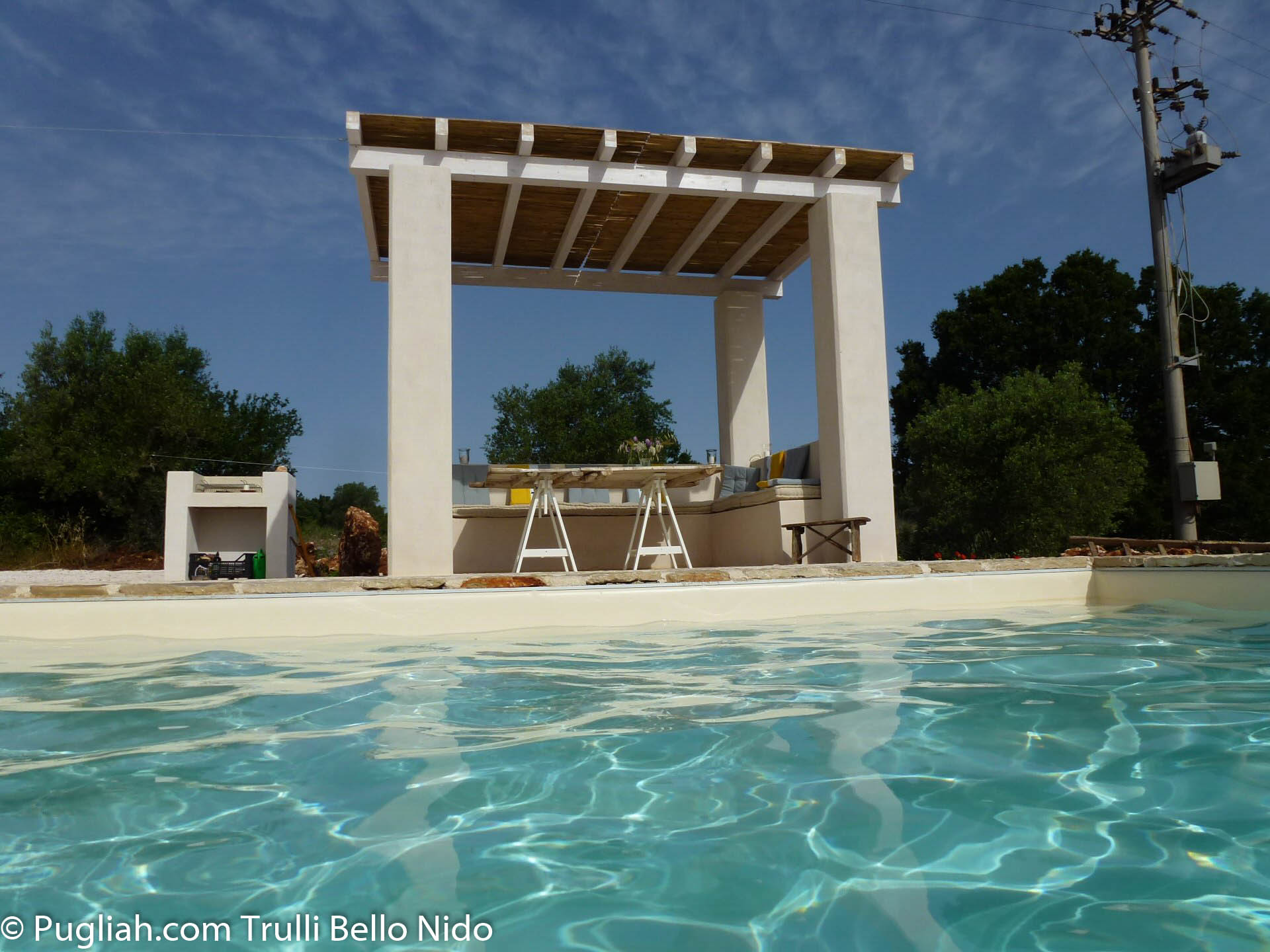 Shaded poolside pergola with seating/dining