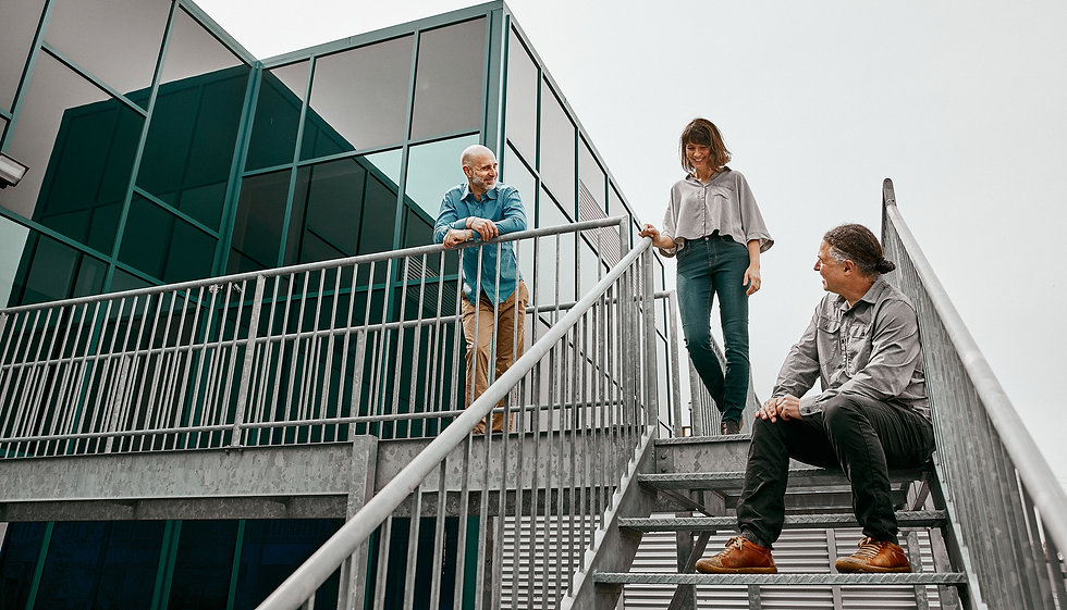 In the background, Stéphane, Caroline and Laurent lean against a metal railing.
