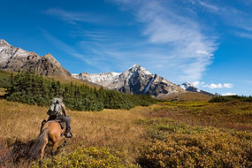 man on horseback riding through mountains