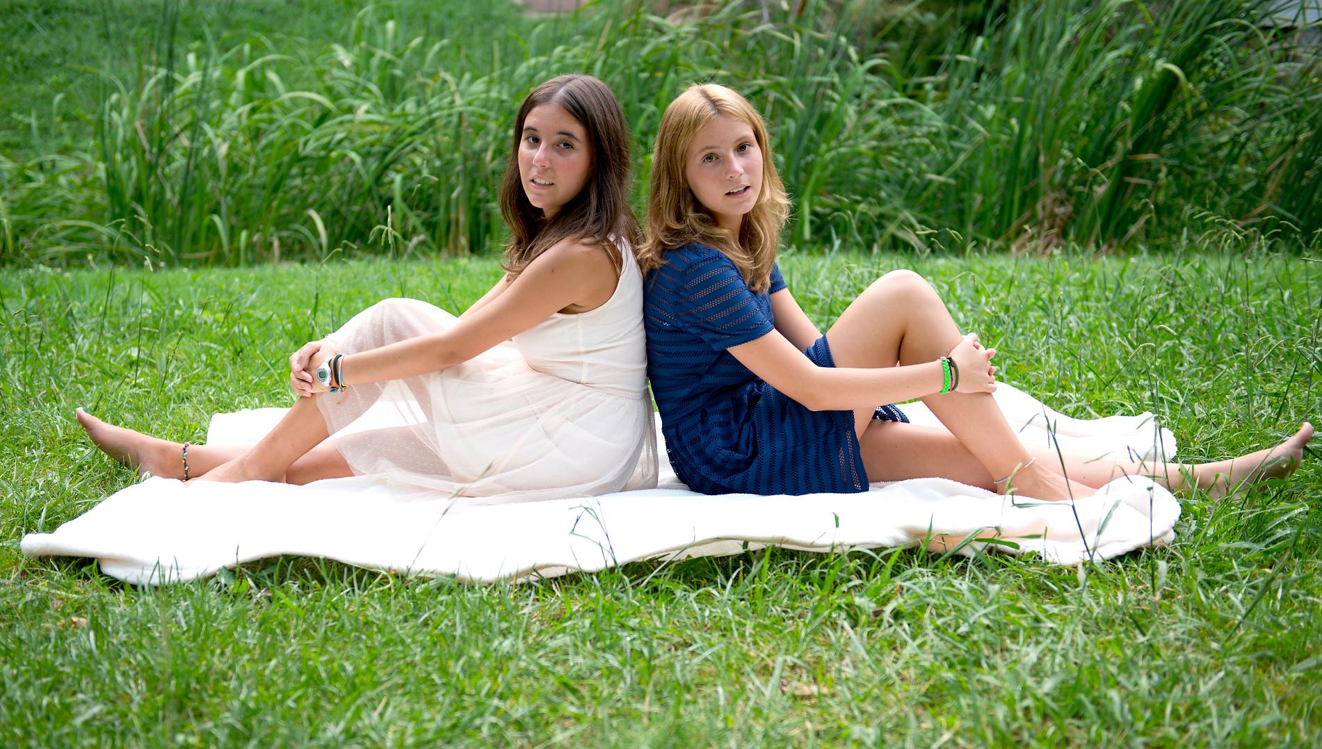 Fotografía de dos niñas sentadas en la hierba