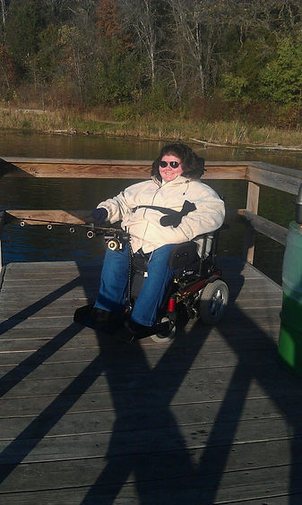 Sarah is seated in her power wheelchair and bundled in a tan colored, heavy winter jacket with navy blue mittens on. Propped on her lap is an electric fishing rod, cast out into the lake over the edge of the dock.