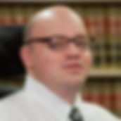 Photo of Michael Wasser. He is bald, wearing black rimmed glasses and slightly smiling at the camera. He wears a white collared, button up dress shirt and a grey paisley tie.