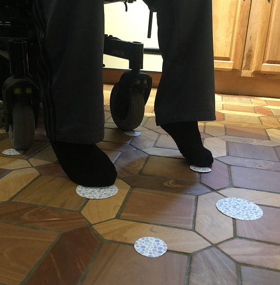 Polka-dot colored circles on a tile floor create a path. Two wheelchair castor tires are on the two circles in the far part of the path. Two feet are on top of the circles in the middle. Two circle remain untouched in the foreground.