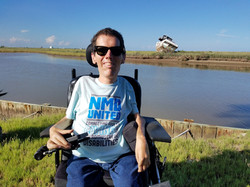 Man sitting in powerwheelchair in front of a body of water, wearing a NMD United shirt