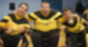 Three men in yellow and black jerseys with their arms around each other and large grins on their faces sit in their power soccer wheelchairs.