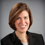 Close up photo of Kareen Zeitounzian. She has short brown hair, brown eyes and is smiling at the camera. She wears a white blouse, a black collared blazer on top, and a string of pearls around her neck.