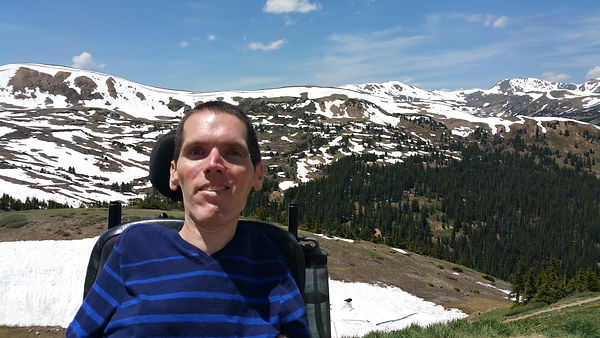 Danny is sitting in his power wheelchair facing the camera. He is wearing a blue striped shirt and a large grin. He has short brown hair. He is pictured outside with a snowy mountainous landscape behind him.