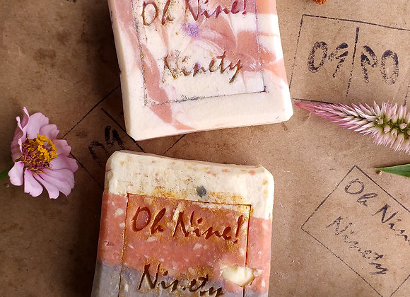 Oh Nine! Ninety creations soap set on brown logo-stamped paper surrounded by flowers..